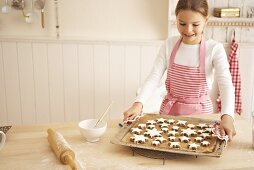 A girl holding a baking tray of cinnamon stars