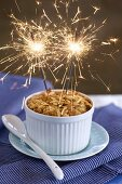 An apple crumble with two sparklers