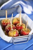 Toffee apples covered with chopped nuts in a pan