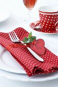 A place setting with a polka dot napkin and a strawberry-shaped label
