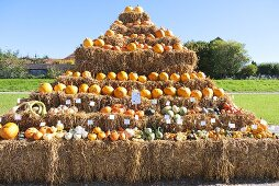 A hay bale pyramid with lots of different types of squash