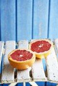 Pink grapefruit, halved, on garden chair