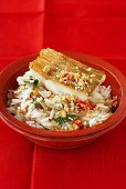 Fried zander on rice with peanuts and chilli