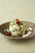 Couscous with vegetables, fried bacon and yoghurt sauce