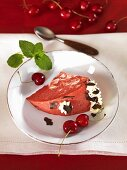 A piece of red and white ice cream bombe