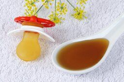 Spoonful of fennel honey syrup beside a dummy