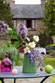 Spring flowers in small watering can on garden table