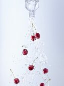Water and cherries pouring out of bottle