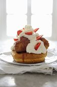 St. Honoré cake with profiteroles, cream and strawberries