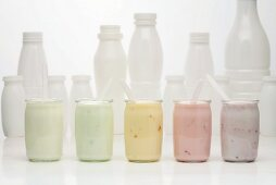 Jars of different yoghurts in front of plastic bottles