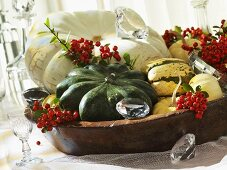 A wooden bowl filled with pumpkins and firethorn berries as autumnal decoration
