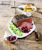Roast beef with cucumber salad, salsa and potatoes