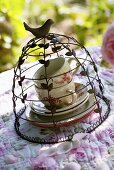 Teacups under decorative cover on romantic table