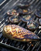 Marinated duck breast and mushrooms on a barbecue
