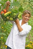 Woman holding wire basket of organic vegetables in garden