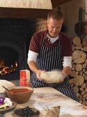 Pizza baker kneading dough