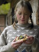 Young woman eating pizzette with pear, radicchio & Gorgonzola