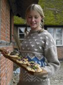 Young woman serving pizzette on wooden tray