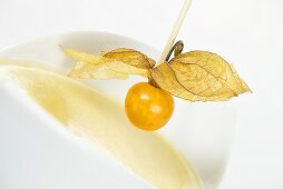 Physalis on wooden cocktail stick over white chocolate sauce