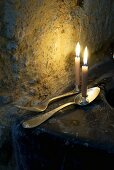 Burning candles on silver spoon and fork