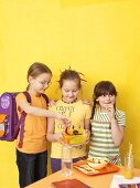 Three children with a packed lunch