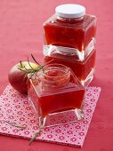 Several jars of strawberry and apple jam