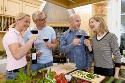 Kitchen scene: two couples clinking glasses of red wine