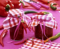 Paprika sugo in jars with checked fabric covers