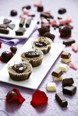 Pieces of chocolate and chocolate buns with rose petals