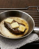 Steak with pieces of butter in a frying pan