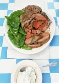 Cooked leg of lamb with garlic sauce and mangetout