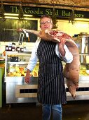 A butcher carrying half a pig on his shoulder at a Farmer's Market in England