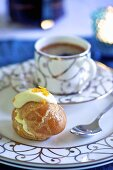 A profiterole with white chocolate and a cup of coffee