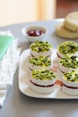 Mini Camembert cheeses with strawberry jam and pistachios