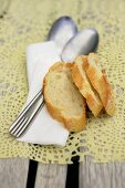 Slices of baguette, spoons and a napkin