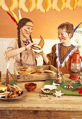 Two children dressed as Indians eating hamburgers at a party