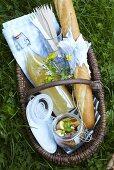 Picknickkorb mit Saft, Baguette und Kartoffelsalat