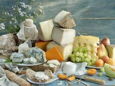 An arrangement of various cheeses, grapes and pears
