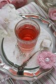 A glass of rosehip tea, silver balls and a crocheted flower