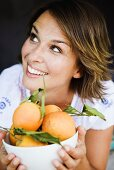 Young woman holding a bowl of fresh oranges