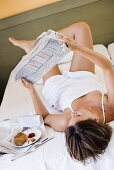 Young woman lying in bed reading newspaper