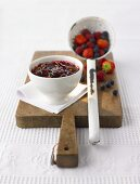 Mixed berry jam in a small bowl, fresh berries in ladle