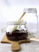 Raspberry & blueberry jam in jar with sprig of rosemary