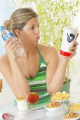 Woman with snacks, cola and bottle of water