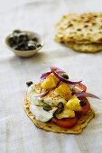 Naan bread topped with tomato, pineapple and capers