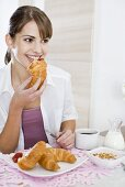 Young woman eating a croissant for breakfast