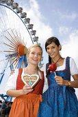 Two women in front of big wheel (Oktoberfest, Munich)