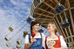 Women in dirndls with toffee apple & Lebkuchen heart (Oktoberfest)