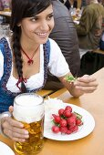 Woman with snack & beer sitting at beer table (Oktoberfest)