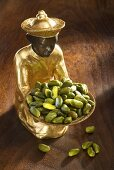 Gilded statuette with shelled pistachios